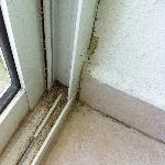 terra e sabbia sulle guide della porta finestra(all'interno della stanza)