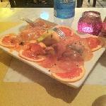 carpaccio di salmone e spadi freschi, serviti con pompelmo rosa e bacche di ginepro