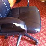 the chair with ripped arm rests on both sides.