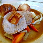 Roasted pork garnished with cabbage, carrots, roasted potatoes in horseradish sauce.