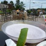 A delicious martini with a glipse of the outdoor seating and awesome fire pit!