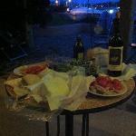 cenetta sul patìo a pane carasau, pomodori, olio e un bicchiere di vermentino