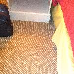 Dirty carpet on other side of bed