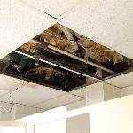 Above the showers, there was a missing ceiling panel, revealing dirty pipework that dripped onto