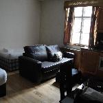 La vue depuis l'entrée, le lit simple à droite, le canapé, et un morceau du lit double