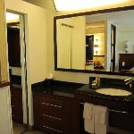 small mirrored closet to the left of bathroom sink
