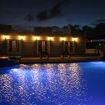 Facing the St. Christopher Club pool house at night, the lights of the pool change colour (fade)