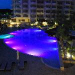 The pool area at night time with colour changing lights in pools