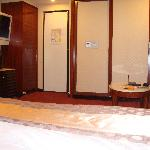 Room door, TV, couch, bathroom (behind the sliding wall) and foot of the bed