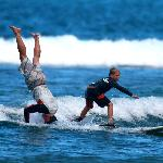 Younger brother surfing beside one of the talented instructors