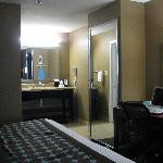 large vanity with two floor length mirrors in room