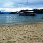 Playa de una isla con embarcacion de fondo