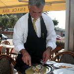waiter preparing our delicious fish