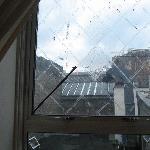 fenêtre cassé, vue sur les déchets balancés sur le toit