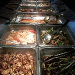 Various entees & side dishes, baked fish in center
