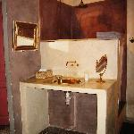 The copper sink in the room, with the shower behind it. Toilet is on the left hand side