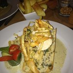 chicken with garlic and basil cream sauce on toasted ciabatta  decorated with vegetable crisps