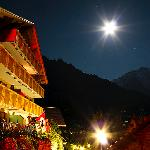 Small road leading to hotel at night. In the distance is the peak of Jungfrau.
