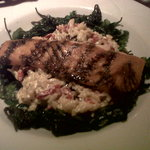 Salmon with red pepper orzo in a creamy cheese sauce and crispy fried spinach