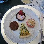 spinach quiche, yogurt with fresh fruit and spices in a dark chocolate cup, roasted tomato drizz