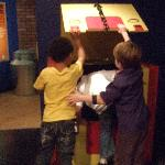 Children playing the Metamorphosis trick in the A.K.A. Houdini exhibit.