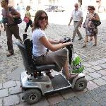 Guide demonstrating scooter in Prague on cobblestone streets.