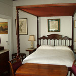 The front bedroom of the Cottage at Stone House features this antique full-size canopied 'spool'