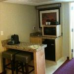 Microwave, refrigerator and bar area.