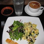 Scrambled eggs, mesclun salad,baguette, latte, homemade plum jam