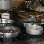 Cottura delle pietanze sui fornelli della cucina esterna.