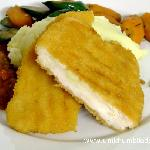 Chicken Schnitzel served on a bed of creamy mashed potato and roasted vegetables