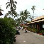 links van de weg de bungalows ; rechts het restaurant en strand