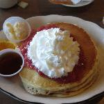 Pancakes with strawberries and whipped cream for breakfast