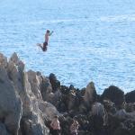 Children jumping off rocks along trail