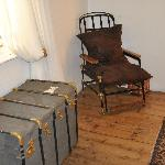 An antique wheelchair used as a bedroom chair