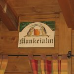 the sign of the Mankei alm with the 'mankeis' represented on the sign
