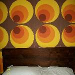 funky 70s wallpaper above bed!