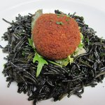 Ball of hake on a bed of squid ink pasta