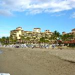 A view of the hotel from the beach.  Dark sand, darker water.