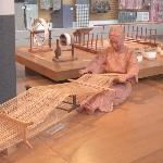 Model of a woman at an old weaving loom.