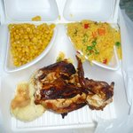 quarter chicken with bun, corn, and yellow rice with vegetables