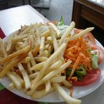 Plato de papas fritas con ensalada completa
