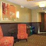 Elevator lobby on each floor has bright colored accent chairs, a window and trash bins.