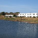 View of the hotel from across the lake.  Rooms are in the tall section, dining areas on the lef