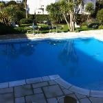 Pool within the hotel grounds. There's seating area around the pool.