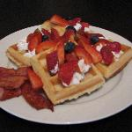 Homemade belgian waffles with cream and fresh fruit with a side of bacon!