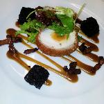 Scotch egg served with black pudding, rocket and frisee salad, pancetta lardons and homemade bro