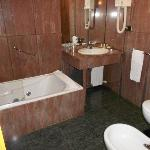 Bathroom, walls completely done in red granite, comfortable tub