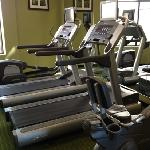 2 treadmills a bike and elliptical machine along with one set of dumbells in the gym