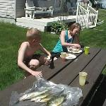 The kids eating lunch while dad was getting ready to clean the fish.